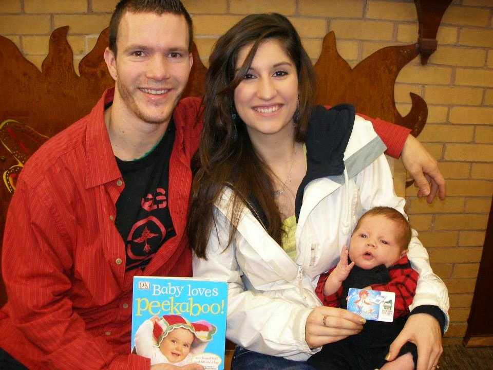 "A man and woman hold a baby with a ""Baby Loves Peekaboo!"" book and library card"