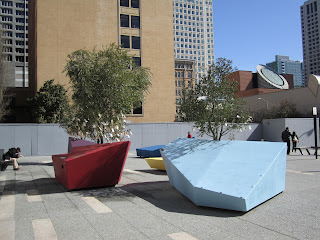a photo of the front courtyard of San Francisco's Contemporary Jewish Museum, with trees whose branches have papers hanging from them.