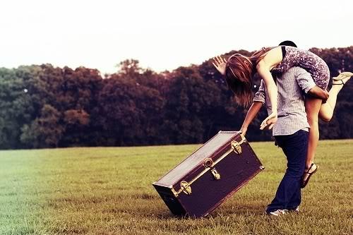 Na foto, um casal se abraçando. O homem está carregando a mulher e puxando uma mala. Eles estão numa ára gramada com árvores no fundo. A imagem, à esquerda, está em preto e branco e fica colorida gradativamente até à direita.