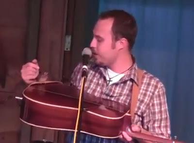 cantante con un pajaro sobre su guitarra