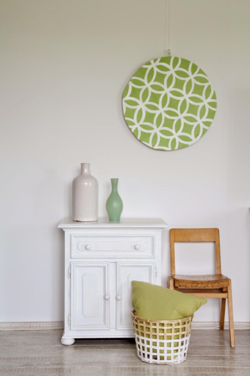 Gesamteindruck grafische Wanddeko mit Kommode und Vasen sowie Korb, Kissen und altem Kinderstuhl
