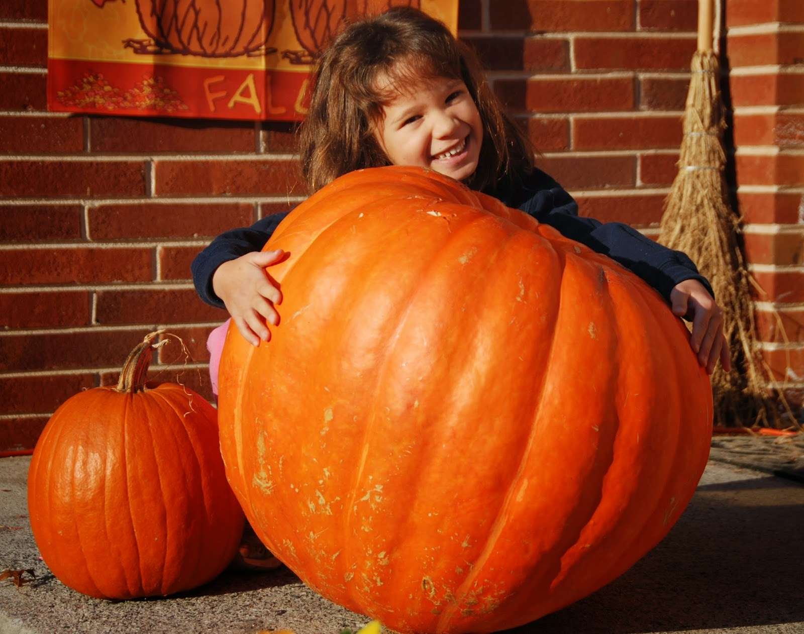 Girl posing with a large pumpkin for Halloween