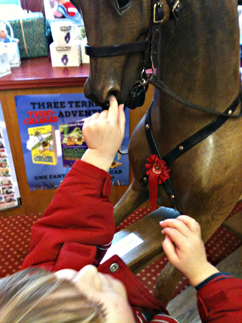 Picking a rocking horse's nose.
