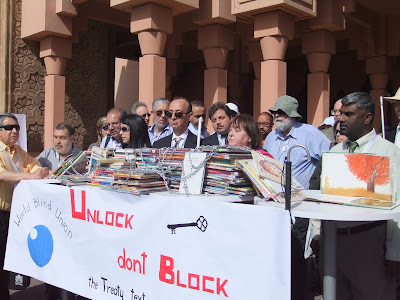 """Action de l'Union mondiale des Aveugles à Marrakech : sur une table, des piles de livres sont couverts de chaines. Sur le panneau disposé en dessous, il est écrit """"Unlock, don't block the Treaty text."""""""