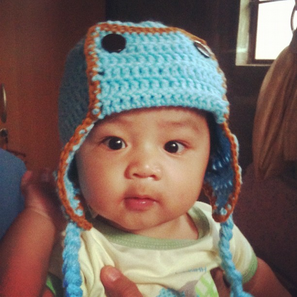 Baby Red wearing a blue hat - crochet kamikaze hat