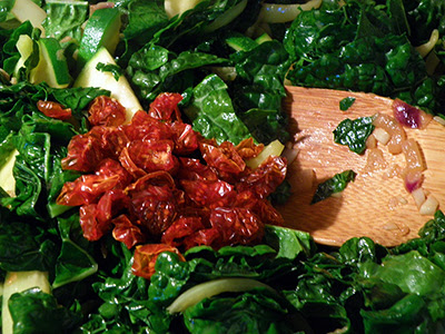 Red dried tomatoes in skillet with Green kale