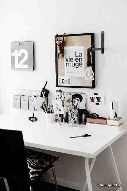 Białe biurko z czarnymi dodatkami, czarna lampka przymocowana do ściany