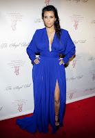Kim Kardashian wearing a blue floor length dress with a deep neckline