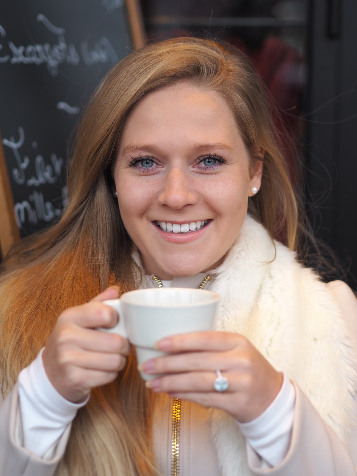 Blonde girl drinking mug of tea wearing fur stole
