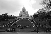 . formidable steps to the foot of the famous monument, where a crowd . (paris montmartre sacre coeur bw)