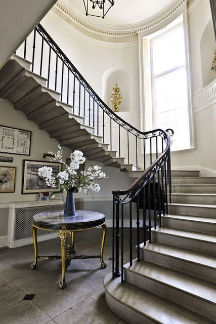 white foyer staircase with gray tile entry white walls