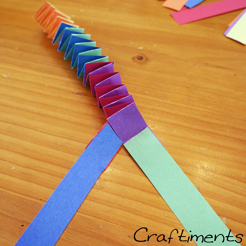 Adding more strips to folded paper garland.