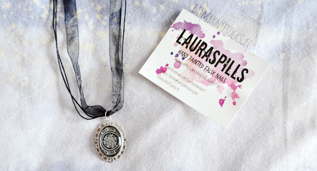 "The necklace from LaurasPills is intricately designed with a vintage vibe. It features a hand-painted glass pendant on a silver metal tray, with a cord-and-ribbon necklace that has a lobster clasp and extender chain. You can adjust it to fit anywhere from 18""-20"" in length, depending on your preference."
