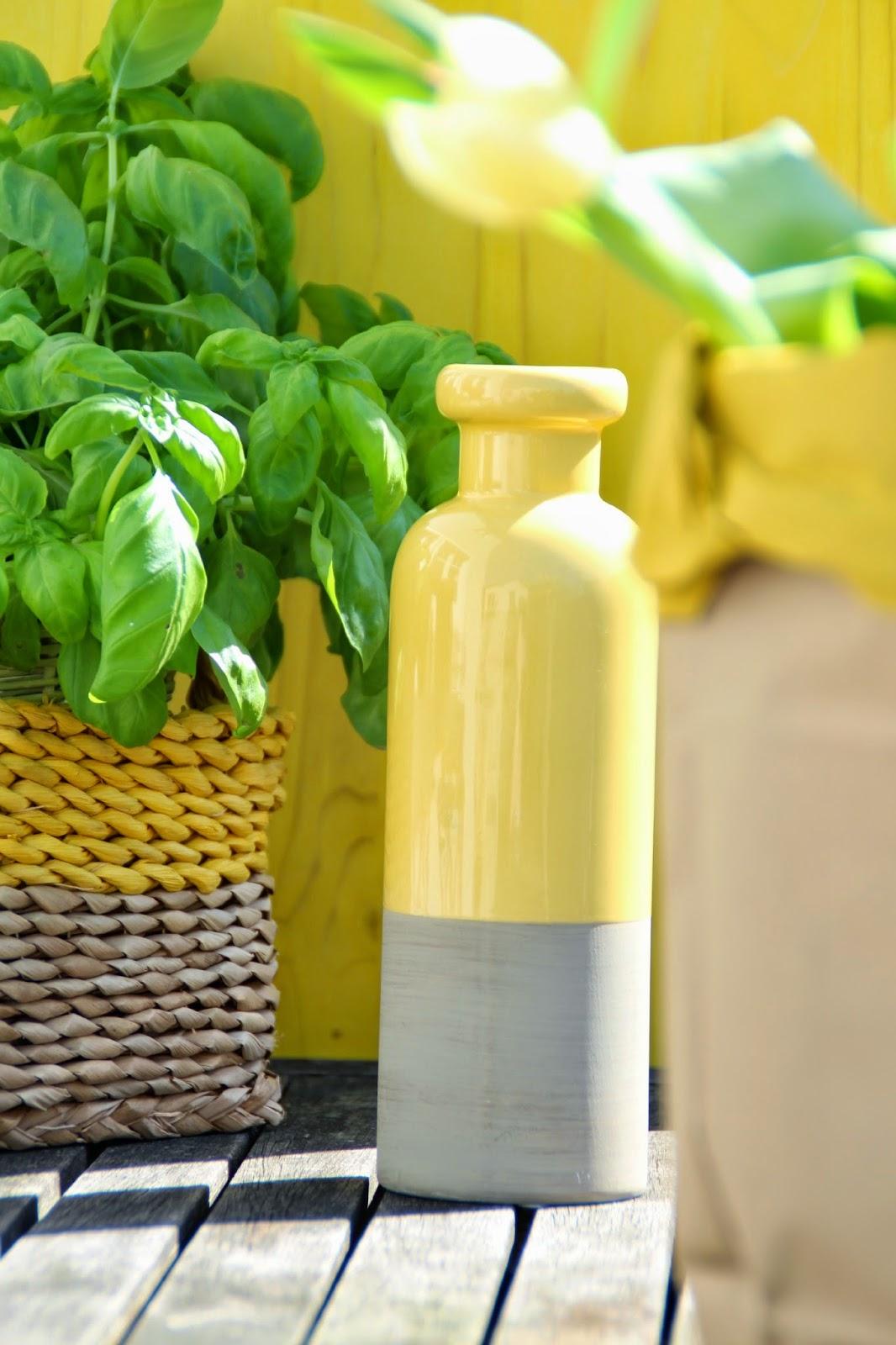 Gelbe Vase mit betonfarbenem Boden und Basilikum in Sisalkorb