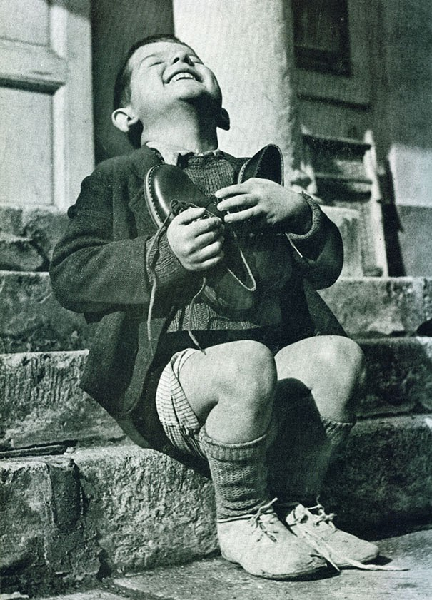 40 Must-See Photos Of The Past - Austrian boy receives new shoes during WWII