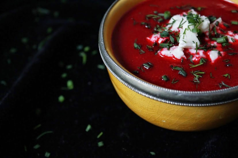 A thick red soup with fresh herbs and cheese