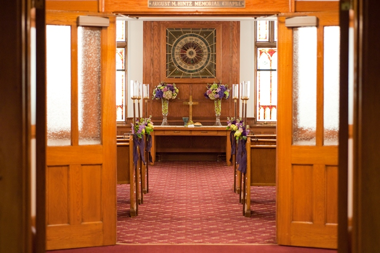 The Pews In Chapel Were Decorated With Tall Hurricane Candle Stands And Small Bouquets Purple Green