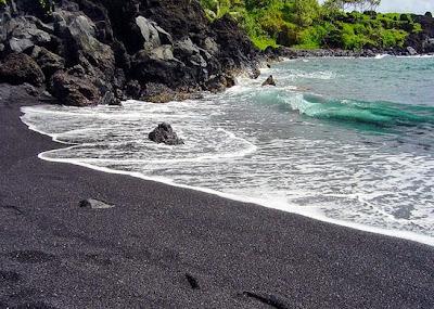 شاطئ لونه اسود ناتج من تفكك الصخور البركانية