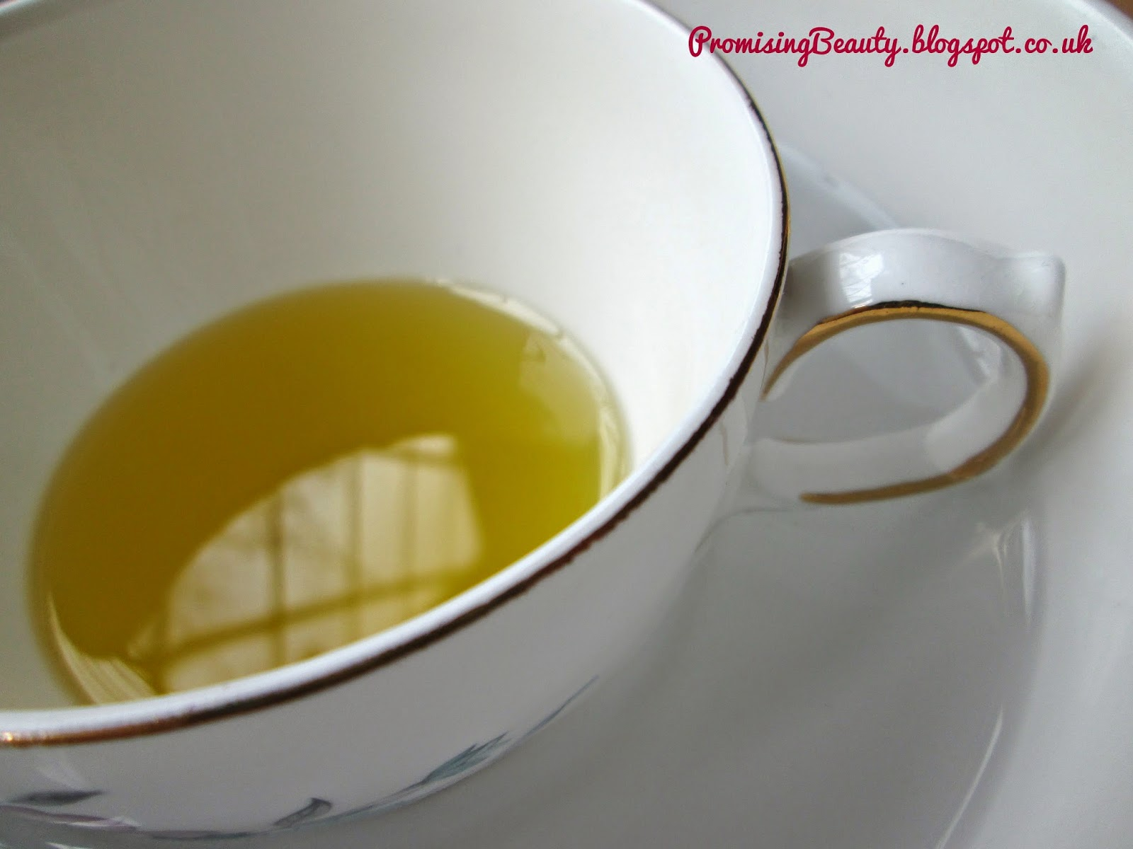 Olive oil being warmed in a teacup and bowl of hot water. Hot oil treatment for dry or damaged hair. DIY beauty from Promising Beauty.