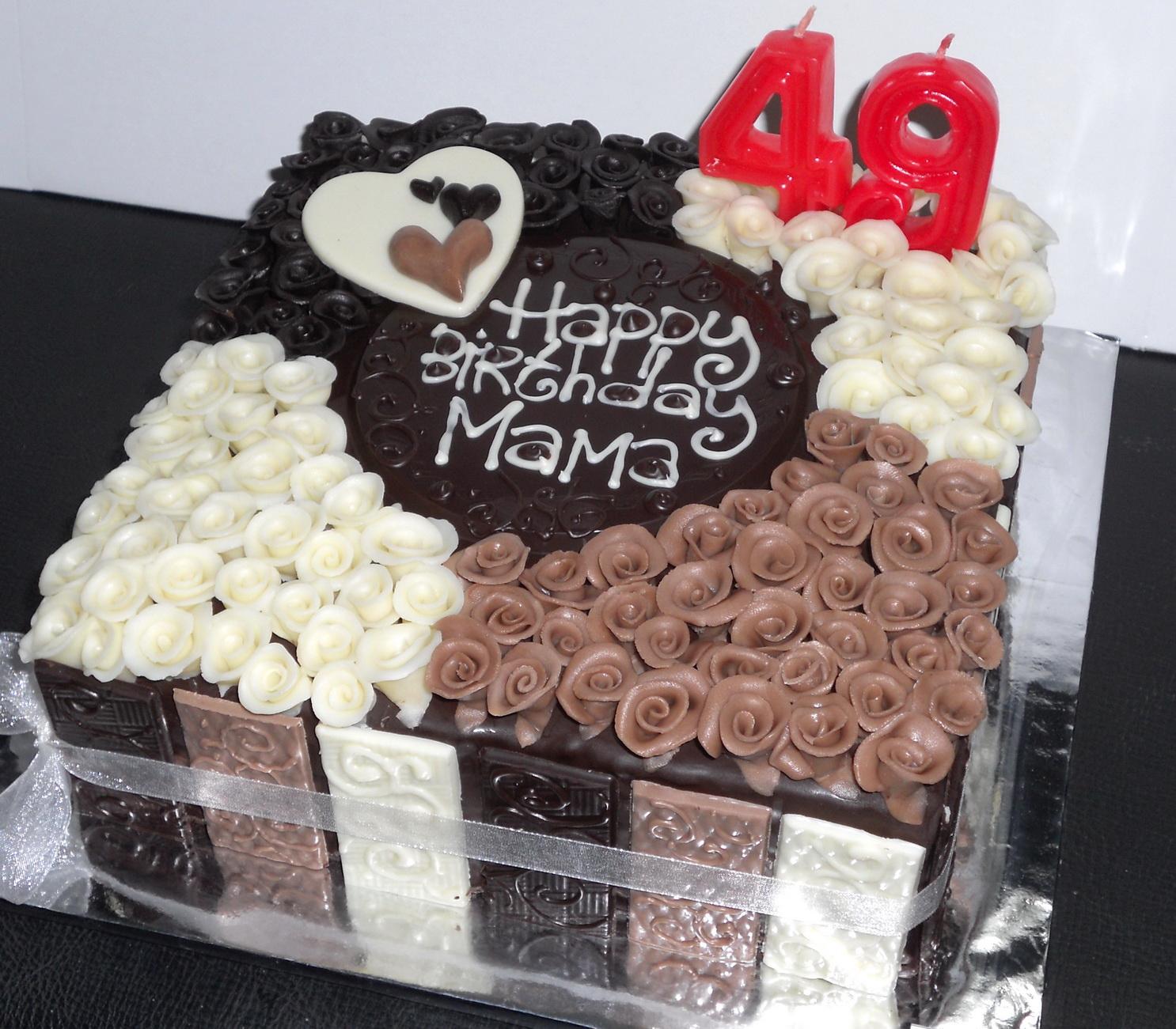 Pesanan cake cokelat dengan bunga-bunga kecil terbuat dari cokelat ...