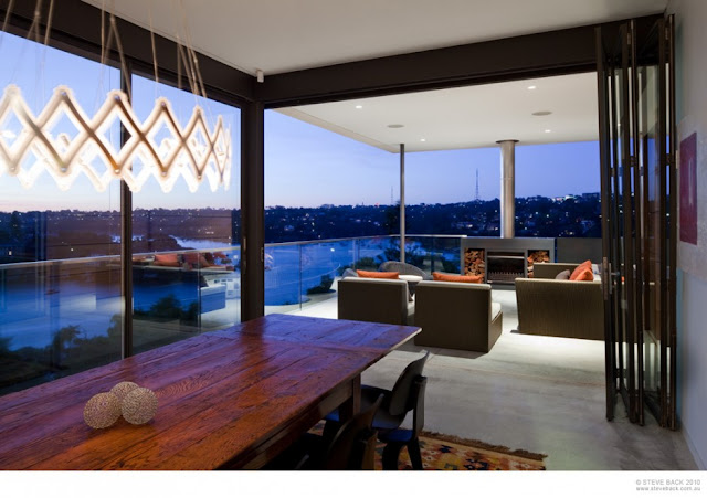 Dining room and terrace at night at River House by MCK Architects