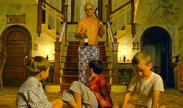 A still from Moonrise Kingdom. Bill Murray stands shirtless with an axe and a bottle of wine in front of three boys.