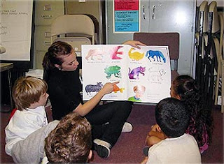 Teacher showing a book of words with picture equivalents to a group of children