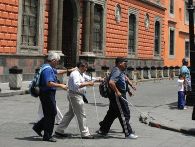 La imagen muestra a tres personas ciegas andando solas por la ciudad con el uso del bastón