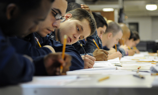 A group of US sailors sitting a written exam