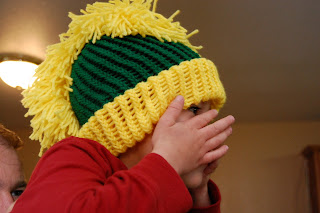 boy with hands up on face wearing a knit mohawk hat