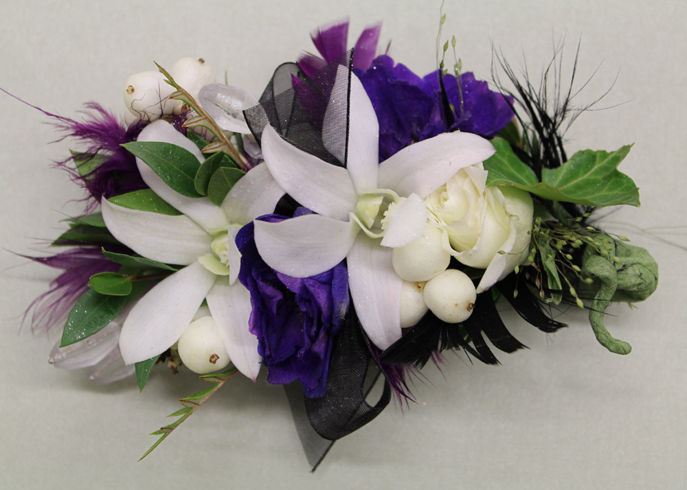 Corsages and boutonnieres this corsage contains purple delphinium two white dendrobium orchids white spray roses oblong crystals snowberries sheer black ribbon and feathers mightylinksfo