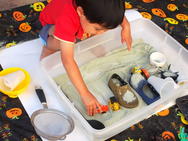 boy playing with colored salt in sensory bin