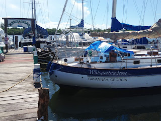 Whispering Jesse in wet storage, with bimini and dodger removed, at Marina del Sol