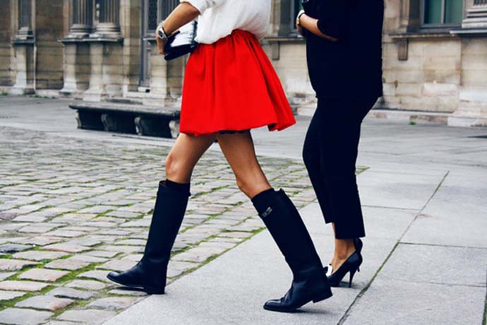 A woman wearing a white top, red short skirt and black riding boots and another one wearing a black blazer, black pants and black pumps