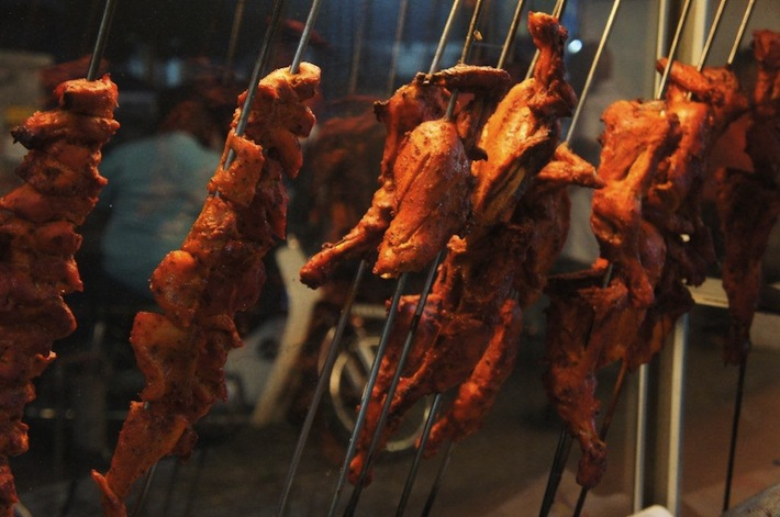 Tandoori chicken skewered on metal rods at a mamak stall in Malaysia