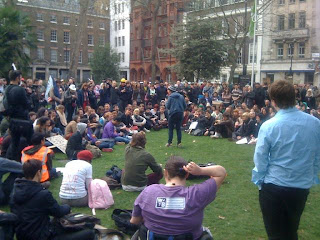 A crowd of a couple of hundred people sitting in a horseshoe shape around Josie Long who is performing. In the foreground there's the backs of me and Johann Hari.