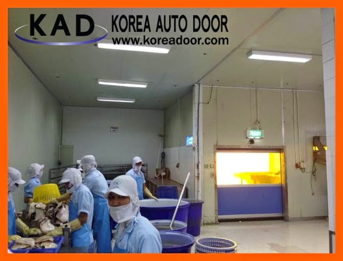 The photo describes a sealing function of high speed door. There are many workers in front of a high speed door with anti-dust sheets.