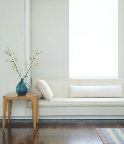 Long window seat with pillows and a wood accent table