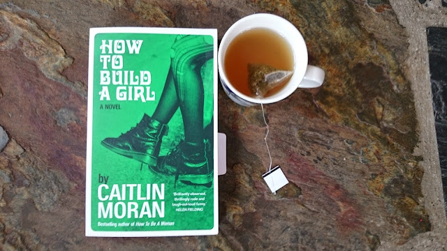 my copy of how to build a girl by Caitlin Moran and a cup of green mint tea that tasted horribly and too much like toothpaste