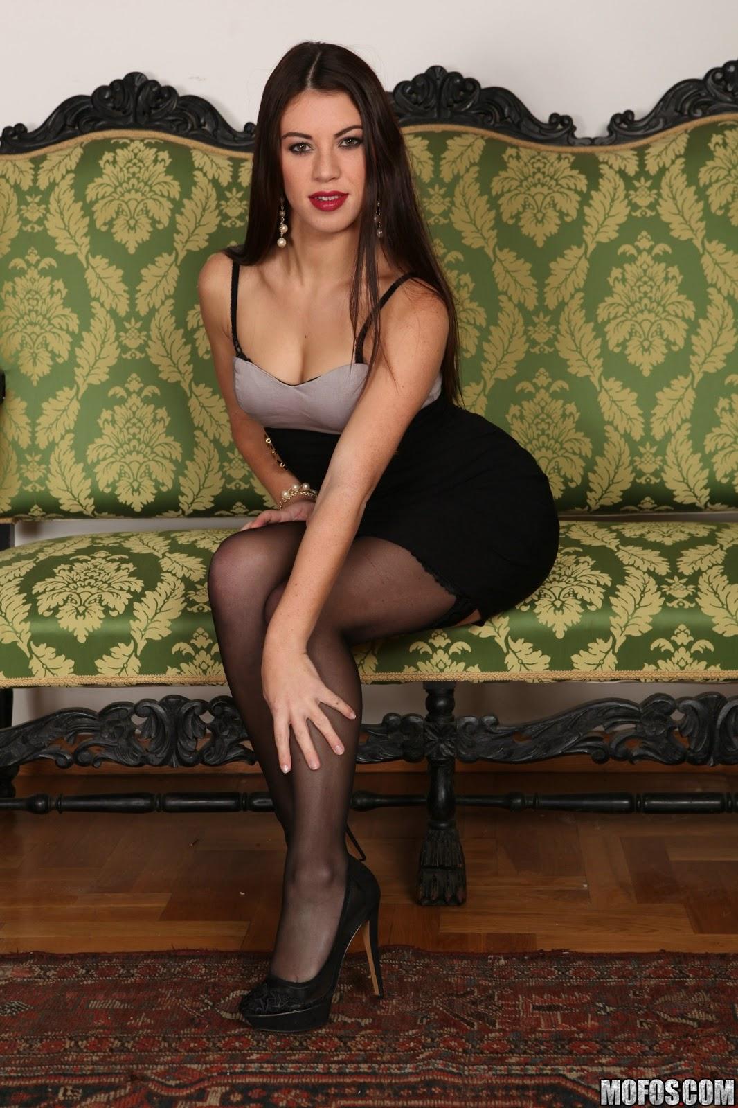 красивая девушка в юбке в черных чулках и на каблуках