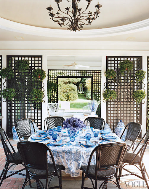 tory burch home estate with trellis garden structures, table cloth on a round table, bistro chairs, blue floral table cloth