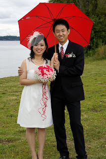 Wei and Shanshan stand under a red umbrella on their wedding day!