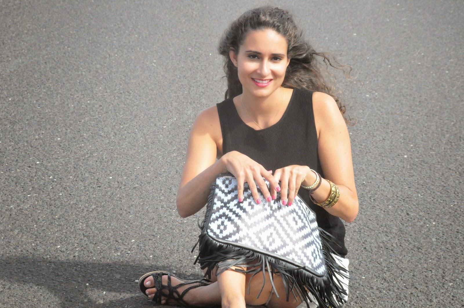 sentada en medio de la carretera con un bolso de mano con dibujos étnicos blancos y negros