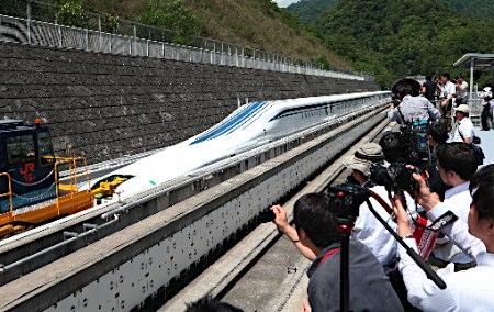 SEJUMLAH orang menyaksikan sebuah kereta api yang terapung di atas landasan di Tsuru, wilayah Yamanashi, kira-kira 100 kilometer dari barat Tokyo semalam.