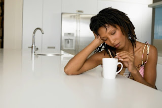 African-American woman looking wistful while stirring her coffee