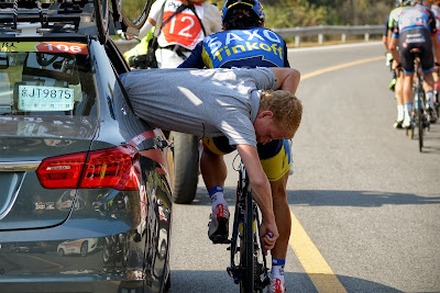 A staff of team Saxo Tinkoff repairs the bicycle for a cyclist as they ride through a country road during the first stage of the 2013 Tour of Beijing cycling race