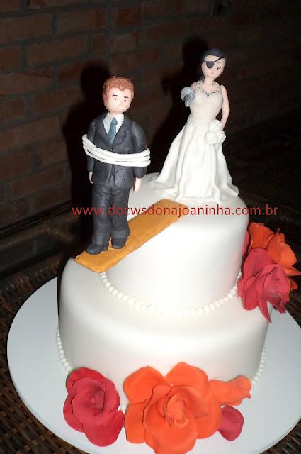 Bolo de casamento com rosas de açúcar e topo de bolo noiva pirata e noivo na prancha