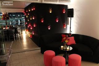 parede fake vidros coloridos, sofá curvo preto, puff redondo pink