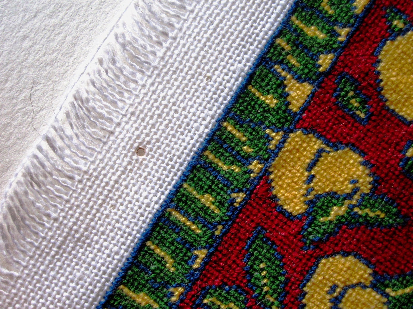 Edge of a piece of cross-stitch fabric with a dolls' house miniature rug stitched on it, showing pin marks from blocking.