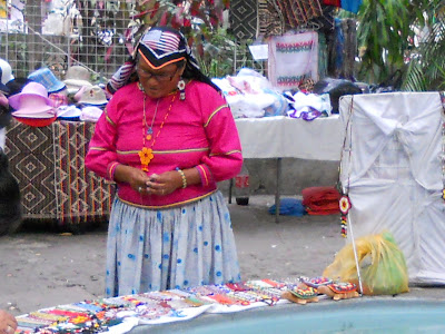 Mexican lady making a colourful necklace with seed beads